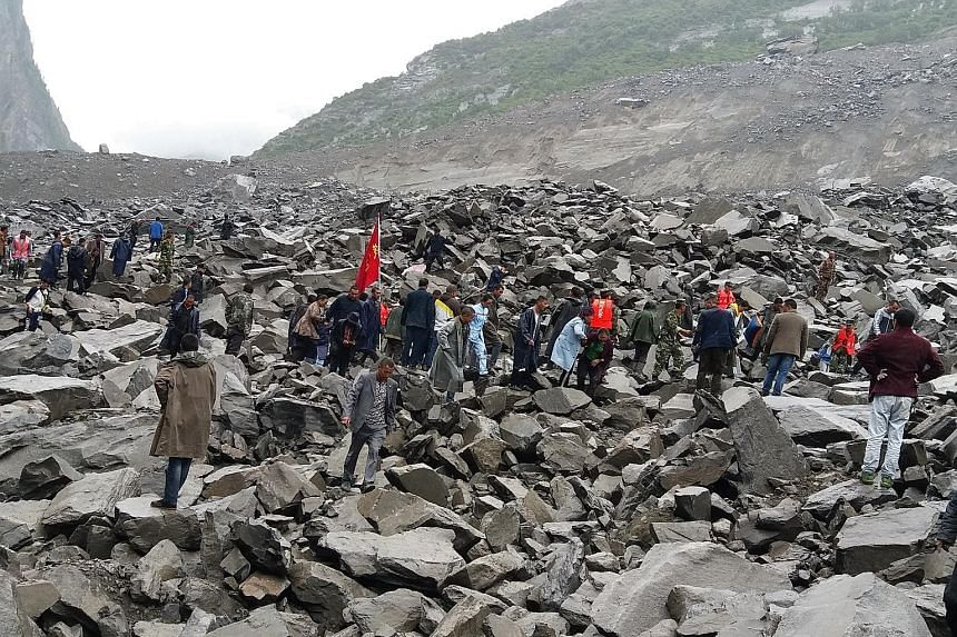 Rescuers searching the rubble for survivors yesterday after 62 homes in Xinmo village, in south-west China, were swallowed by boulders when the side of a mountain collapsed.