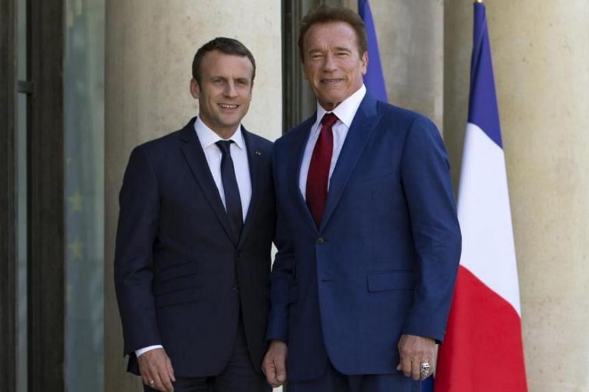 French President Emmanuel Macron (left) greeting R20 founder and former California state governor Arnold Schwarzenegger as he arrives for a meeting at the Elysee Palace in Paris, on June 23, 2017.