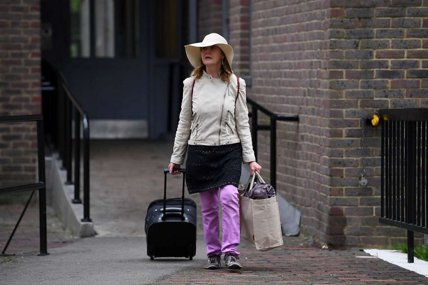 A resident with belongings leaves Taplow Tower residential block on the Chalcots Estate in north London.