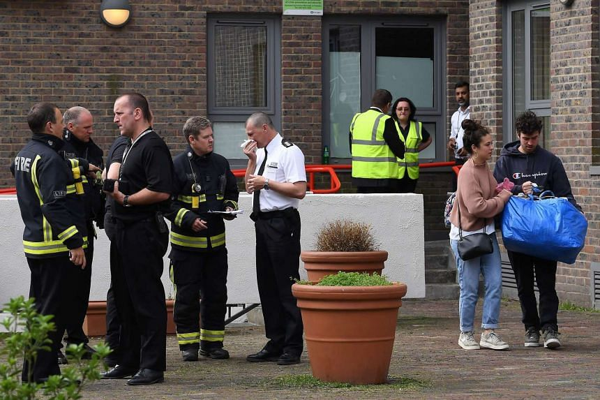 Residents with belongings leave Burnham Tower residential block on the Chalcots Estate in north London.