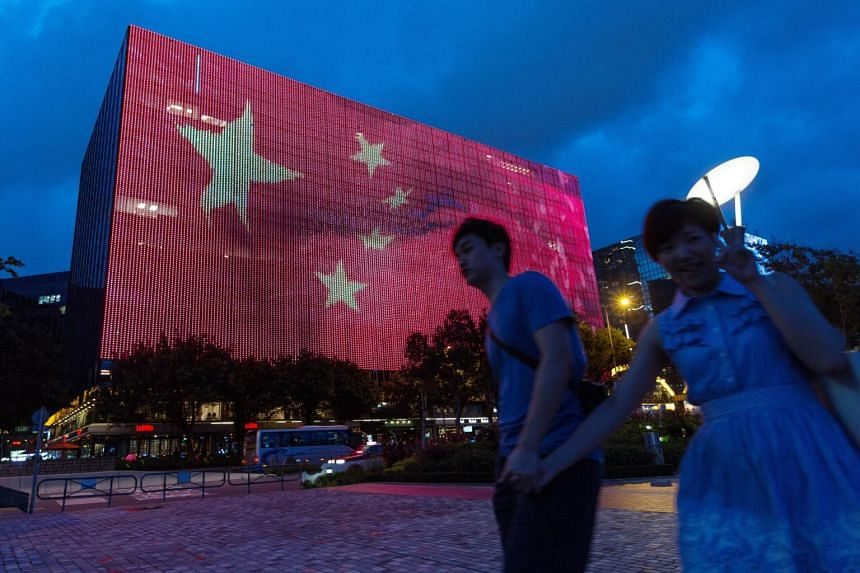A Hong Kong couple walks past a giant electronic billboard showing a Chinese flag on the side of a building in Tsim Sha Tsui on June, 24, 2017.