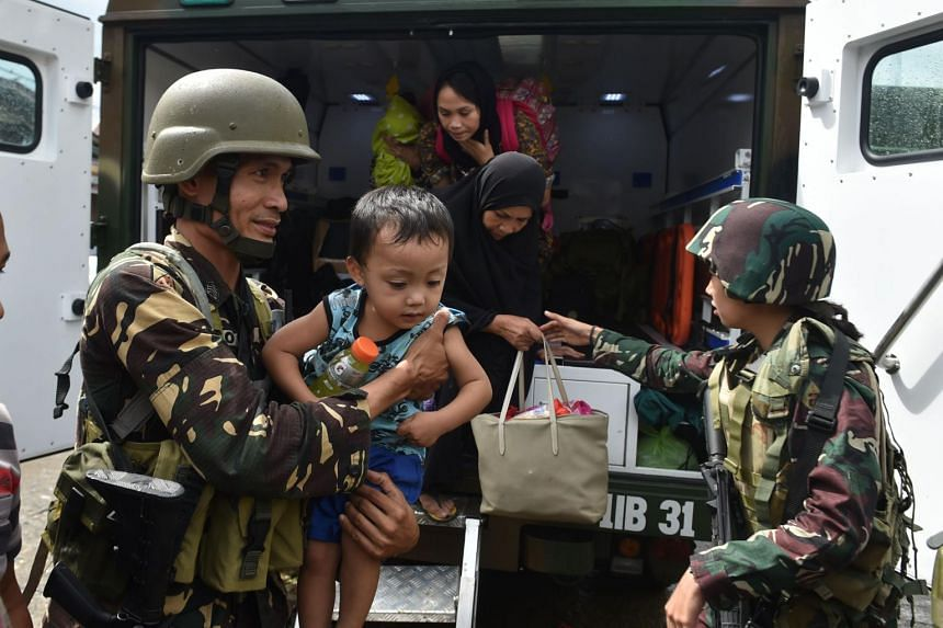 Evacuated residents disembark from a military vehicle shortly after arriving at a processing center near a hospital in Marawi on June 21, 2017.