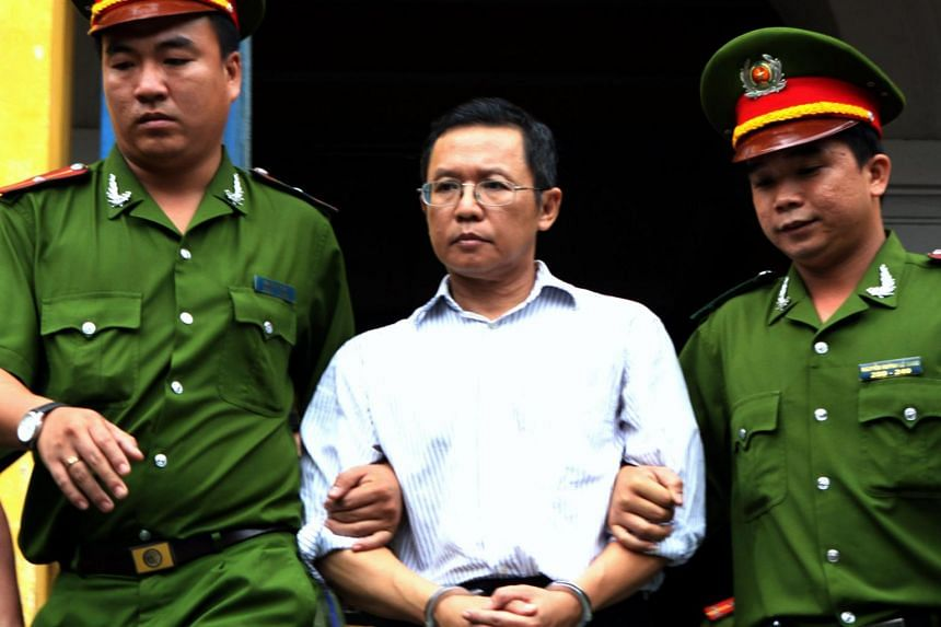 French Vietnamese blogger and lecturer Pham Minh Hoang (centre) being led out from the courtroom at the Ho Chi Minh City People's Court House on August 10, 2011.