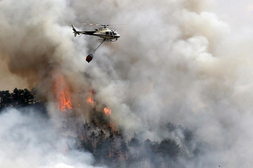 A helicopter works to extinguish a forest fire in Navarra, Spain, on 22 June 2017.