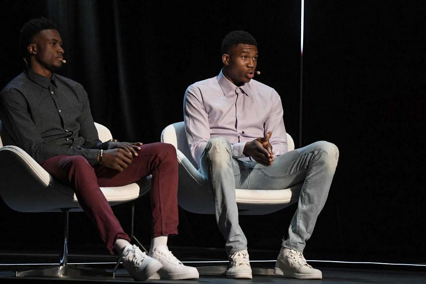 Greek basketball players Giannis (right) and Thanasis Antetokounmpo speaking at the Onassis Cultural Centre in Athens on June 24, 2017.