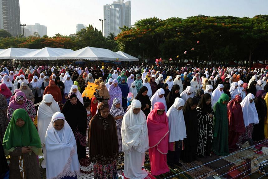Women praying during the start of Eid Al-Fitr prayers, which marks the end of the holy fasting month of Ramadan, at Luneta Park in Metro Manila, Philippines on June 25, 2017.