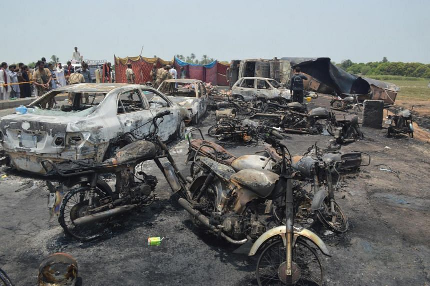 Burnt vehicles at the scene of an oil tanker accident on the outskirts of Bahawalpur, Pakistan, on June 25, 2017.