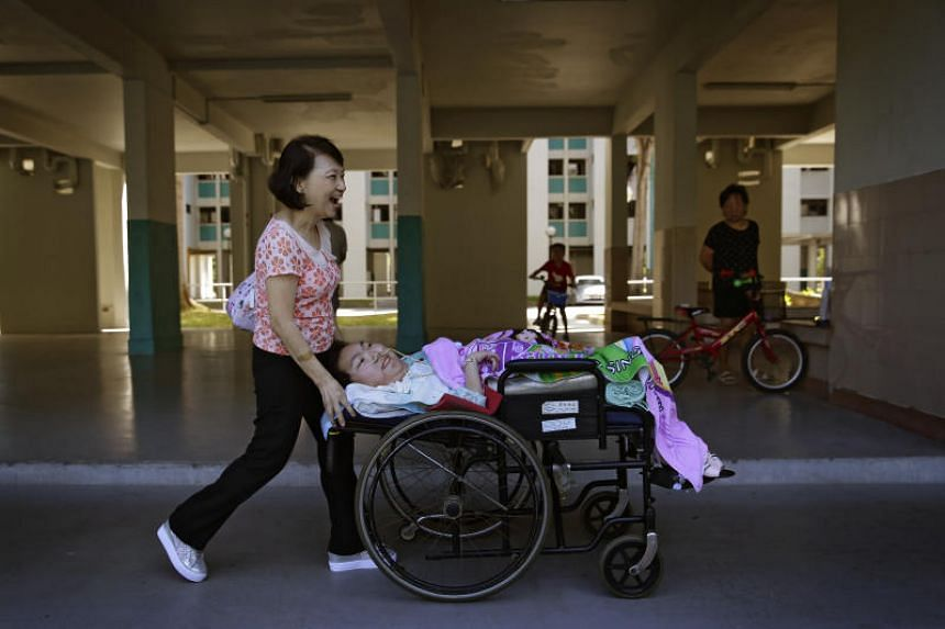 37-year-old Vivian Goh, who has spinal muscular atrophy type 2, a condition that is characterised by progressive muscle weakness, and her mother Ivy Yong, 63, making their way past a void deck to a van that will take them on a rare outing: to the Sin