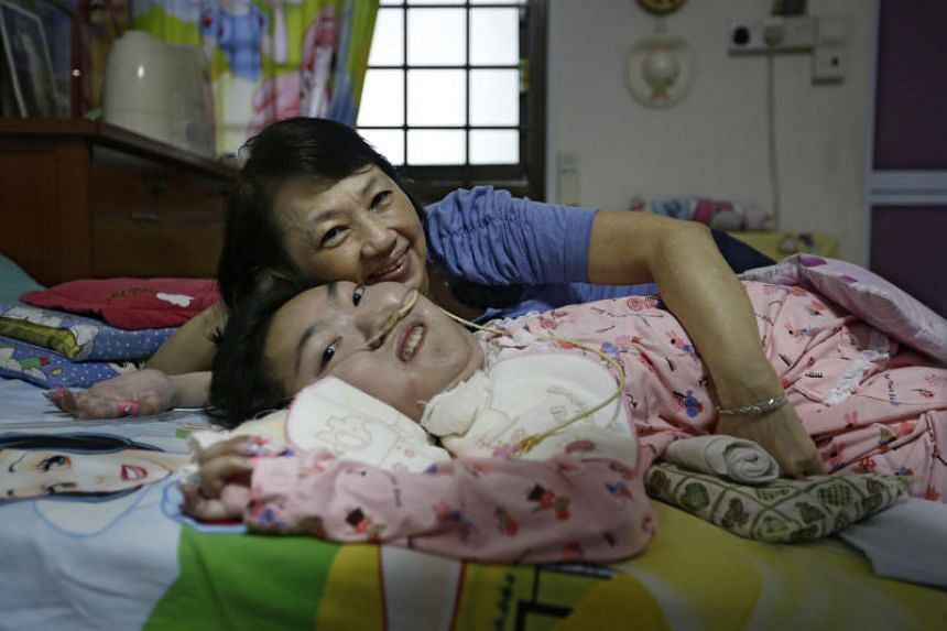 Ms Goh has been cared for single-handedly by her mother since she was three. Her condition has deteriorated gradually throughout her life, and now she can only drink milk through a feeding tube. Phlegm has to be suctioned from her mouth and nose dail