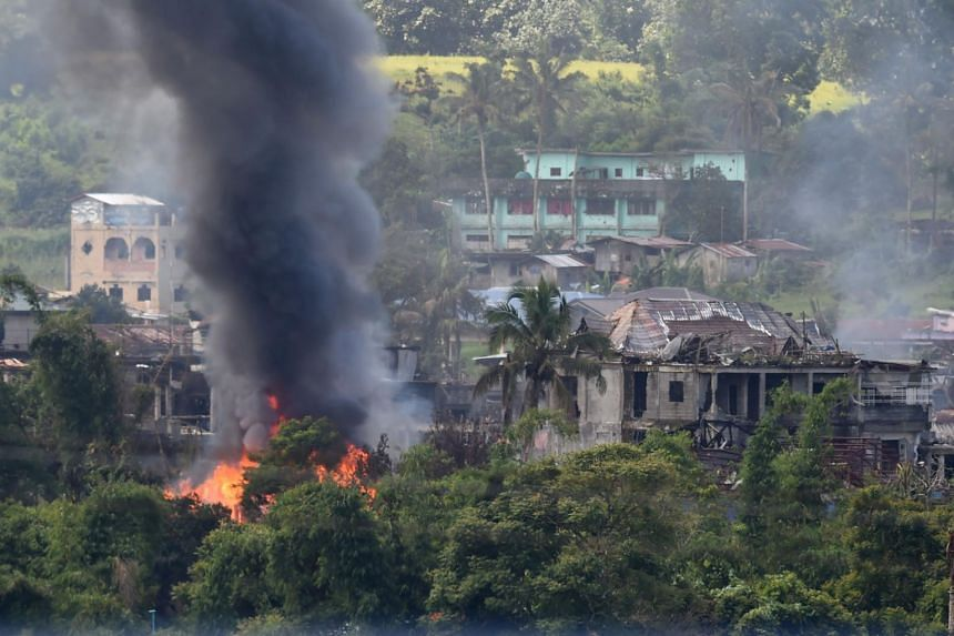 Black smoke billowing from burning houses after Philippine Airforce attack planes conducted aerial bombings on Islamist militants' positions in Marawi on June 26, 2017.