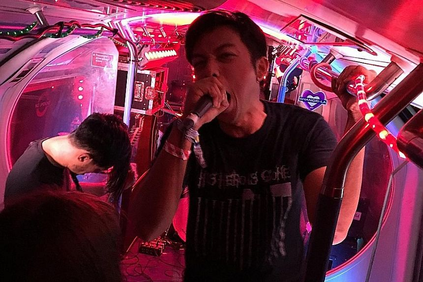 Vocalist Mohammad Arif Suhaimi performing with his band members on the Earache Express, a stage set within a train carriage.