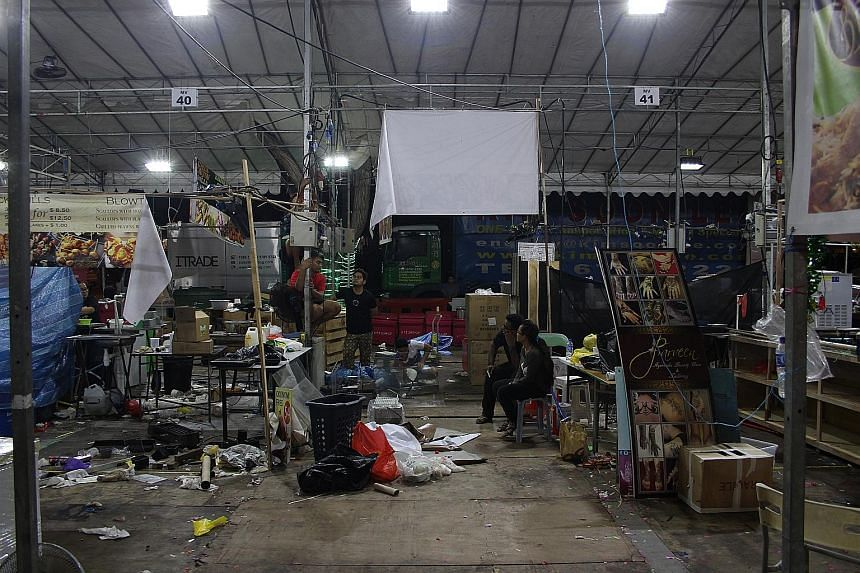 Stalls being dismantled at the Geylang Serai Bazaar just after 5am yesterday as the event drew to an end. Given the high traffic and volume of rubbish usually generated on the bazaar's final night, trash collections are made three times instead of on