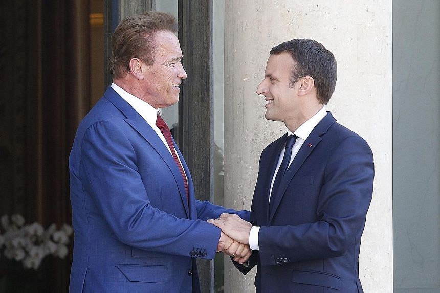 French President Emmanuel Macron with Mr Arnold Schwarzenegger in Paris last week. The US actor turned climate activist is part of a global group seeking to launch a pact to protect the environment.