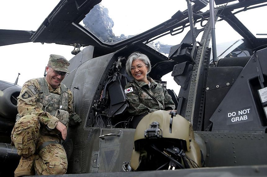 Dr Kang Kyung Wha checking out an AH-64D Apache Longbow helicopter during a visit to Camp Red Cloud at Uijeongbu yesterday. There are hopes that South Korea's new foreign minister, who has successfully balanced work and family, will also break new gr