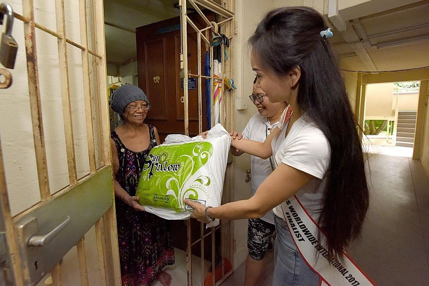 Mrs Chantel Lee, 33, a finalist in the Mrs QOS Worldwide International Singapore beauty pageant, handing a donated pillow yesterday to Ms Rahimah, a Telok Blangah Crescent resident. Ms Rahimah is a beneficiary of Keeping Hope Alive, an informal netwo