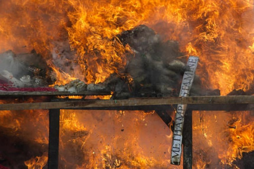 A pile of seized drugs being set on fire in Yangon in this file photo dated June 26, 2016.