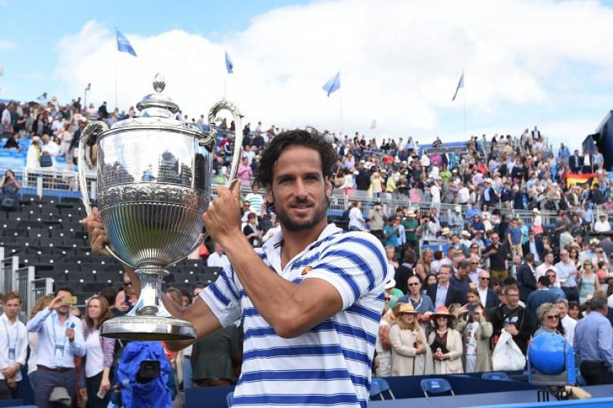 Feliciano Lopez of Spain lifts the trophy after winning the Queen's Club Championships final against Croatia's Marin Cilic of Croatia.