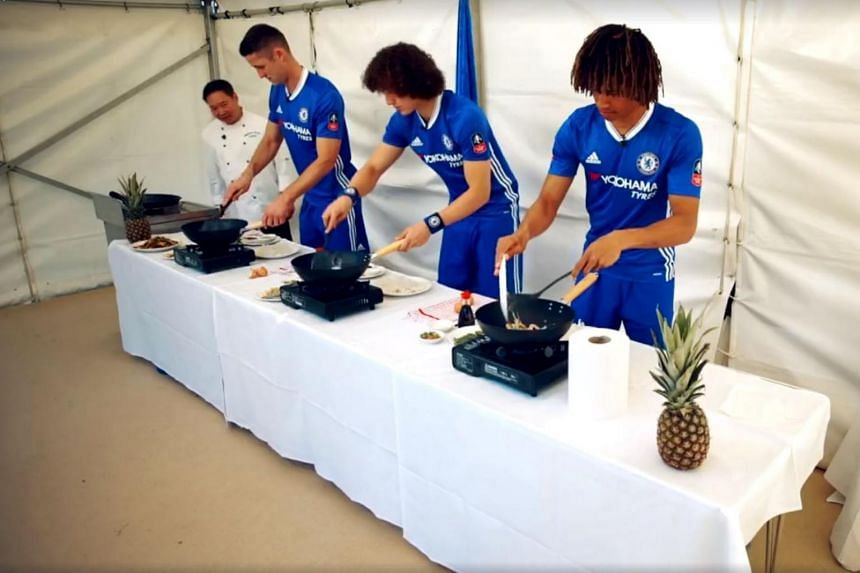 Chelsea players (from left) Gary Cahill, David Luiz and Nathan Ake trying their hand at frying char kway teow while being watched by Singapore Garden head chef Toh Kok Sum.