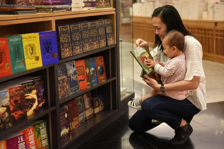 A mother and her child checking out the Harry Potter display at Books Kinokuniya, set up to mark the 20th anniversary of the publication of Harry Potter And The Philosopher's Stone.