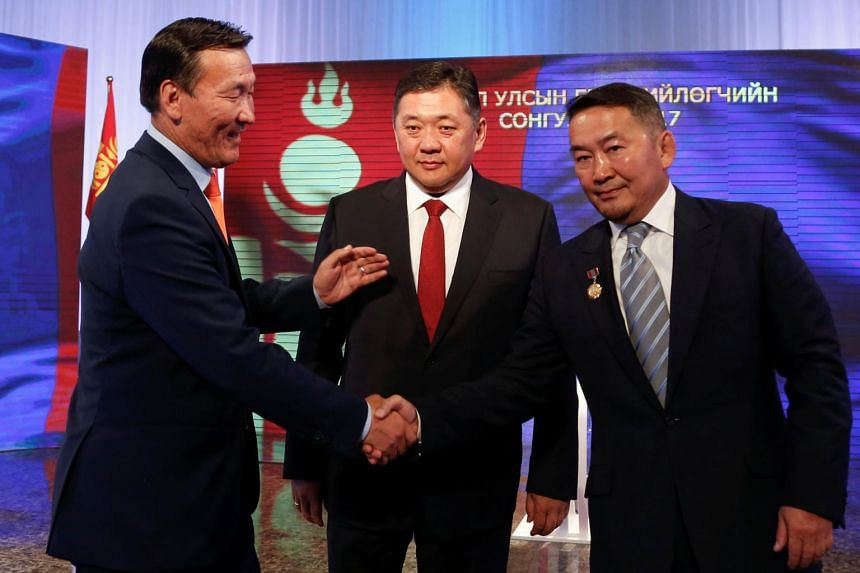 Mongolian presidential candidates (from left) Sainkhuu Ganbaatar, Mieygombo Enkhbold and Khaltmaa Battulga shaking hands before a televised debate, on June 24, 2017.