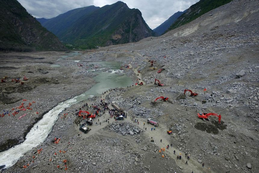 Chinese rescuers searching for survivors at a landslide area in the village of Xinmo in Maoxian county, China's Sichuan province on June 25, 2017.