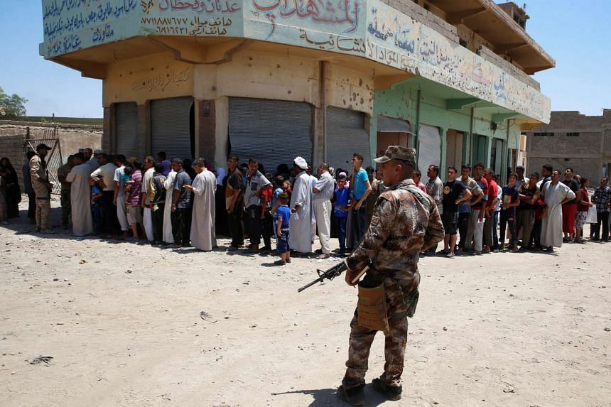 An Iraqi soldier stands guard as displaced Iraqi residents queue for food aid during the first day of the Eid al-Fitr celebration in Mosul on June 25, 2017.