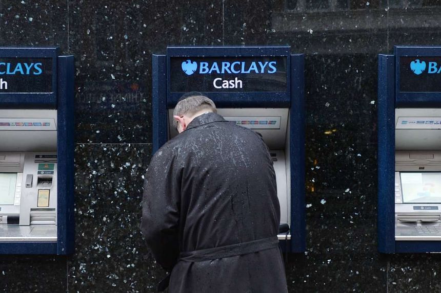 Customers use the ATM machine outside a Barclays bank branch in London. The world's first ATM machine opened at a Barclays branch in Enfield, London on June 27, 1967.