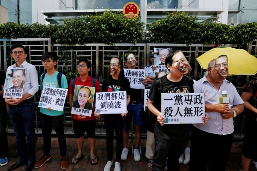Protesters wearing masks of Chinese Nobel rights activist Liu Xiaobo stand outside China's Liaison Office in Hong Kong, China on June 27, 2017.