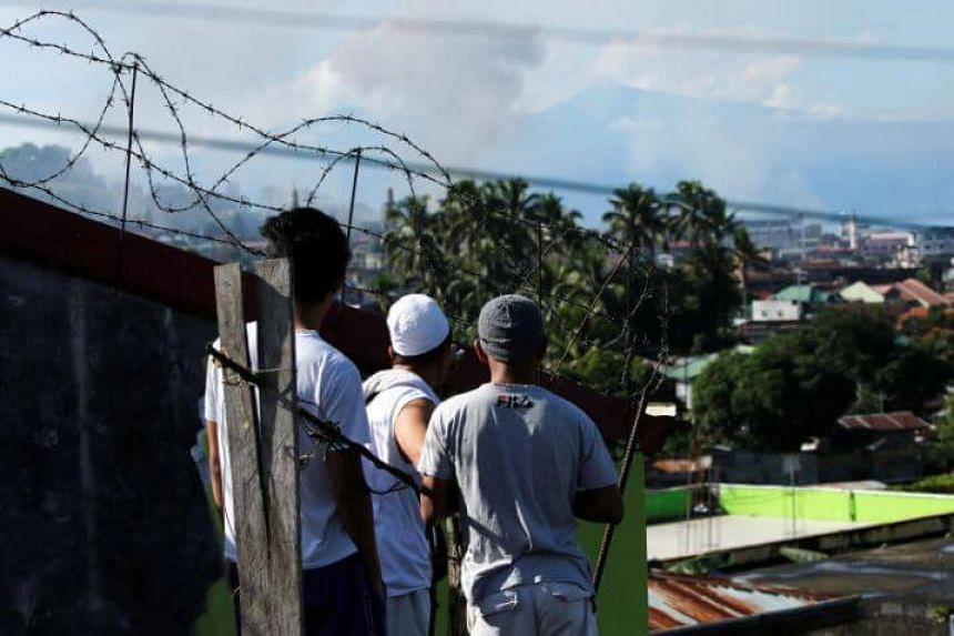 Men watch from a rooftop during the Philippines army airstrike as government troops continue their assault against insurgents from the Maute group in Marawi city, on June 27, 2017.