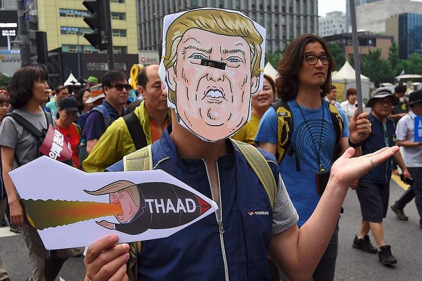 A South Korean wearing a Trump mask protesting in Seoul against the deployment of the Terminal High Altitude Area Defence system.