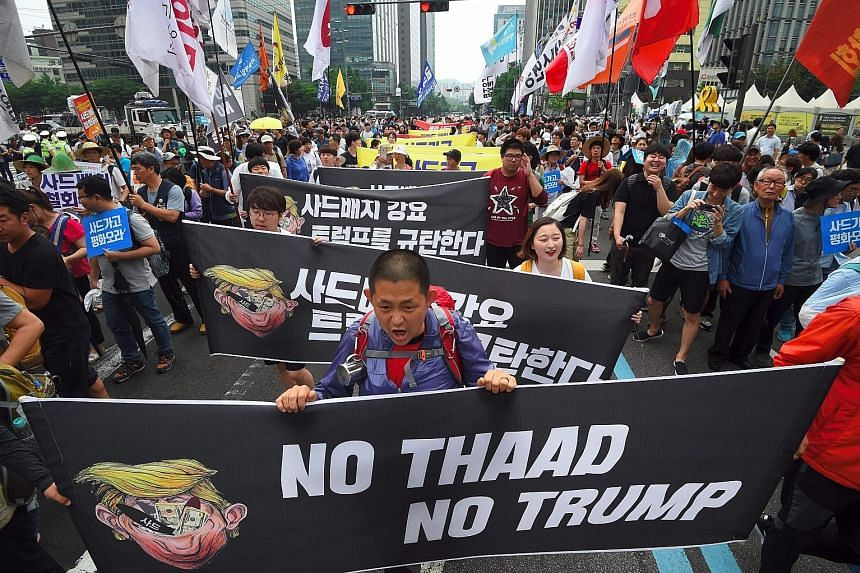 South Koreans protesting outside the US Embassy in Seoul last Saturday against the deployment of the Thaad system, and US President Donald Trump.
