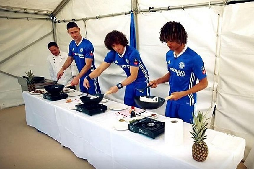 Chelsea defenders Gary Cahill, David Luiz and Nathan Ake (L to R) frying up char kway teow, under the guidance of north London restaurant Singapore Garden's head chef, Toh Kok Sum.