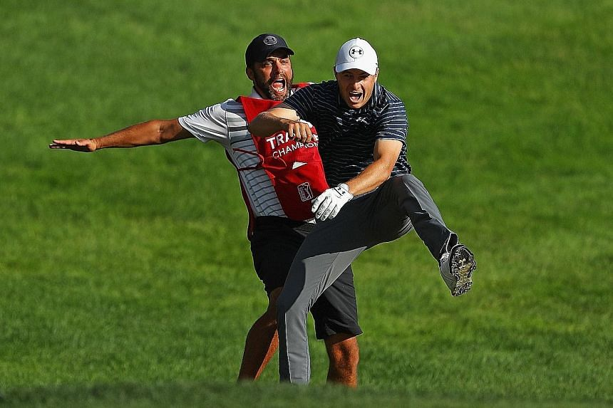 Jordan Spieth enjoying a reverse chest bump with caddie Michael Greller after chipping in for birdie to win the Travelers Championship on the first play-off hole.