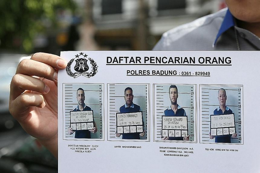 An Indonesian police officer with a release showing photos of the four inmates who escaped from Bali's Kerobokan Prison last week. The incident has highlighted the issue of overcapacity in Indonesia's prisons.