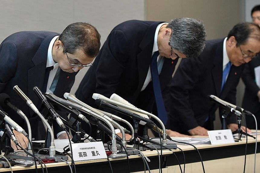 Takata CEO Shigehisa Takada (left) with other executives at the end of a press conference in Tokyo yesterday. Mr Takada said he and top management would resign once the takeover was completed.