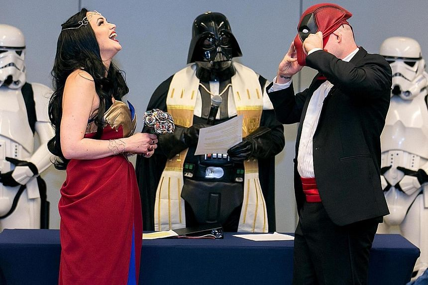 Mr Adam Merica removing his Deadpool mask to address his bride, Ms Megan Mattingly, who was dressed as Wonder Woman at their wedding at Awesome Con in Washington, DC on June 17. Their officiant was dressed as Darth Vader, while the wedding party were