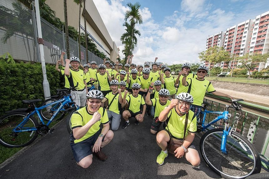 MCC Singapore managing director Tan Zhiyong (far left, standing) with other senior and management staff who took part in a 4km trial ride in Woodlands on June 3. The company will be marking its new initiative with a mass cycling activity ending at Se
