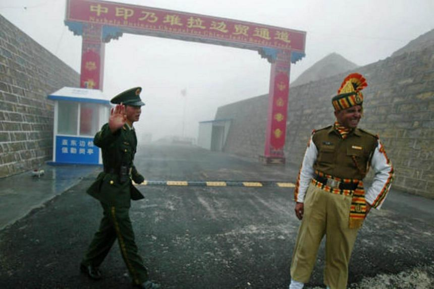 File photo of a Chinese and Indian soldier standing guard at the Chinese side of the ancient Nathu La border crossing between India and China.