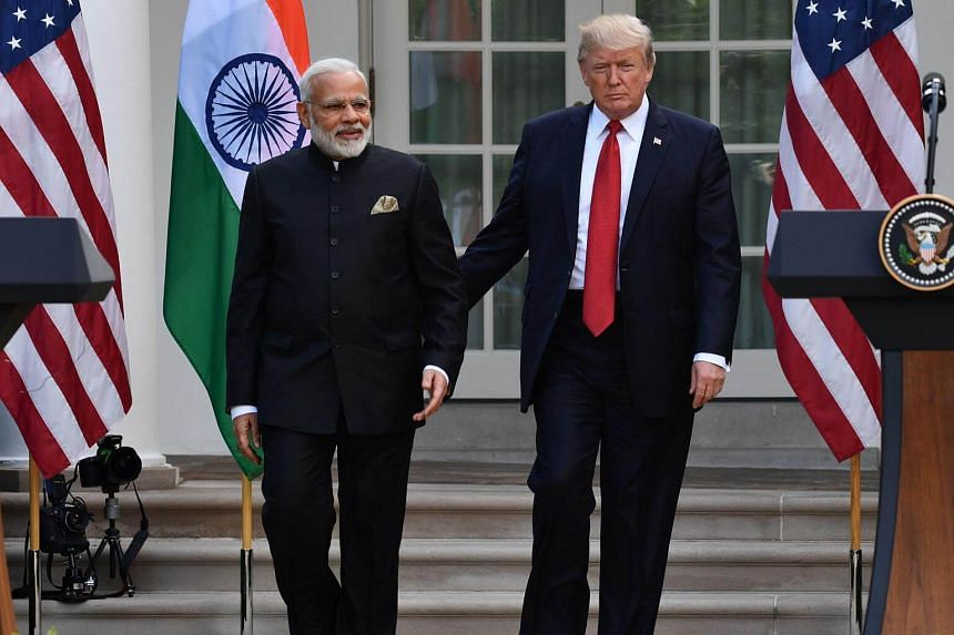 US President Donald Trump guides Indian Prime Minister Narendra Modi towards a joint press conference in the Rose Garden at The White House on June 26, 2017.