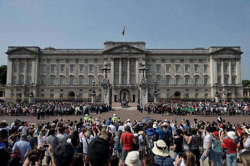 A vehicle carrying the Crown leaves Buckingham Palace for the Palace of Westminster.