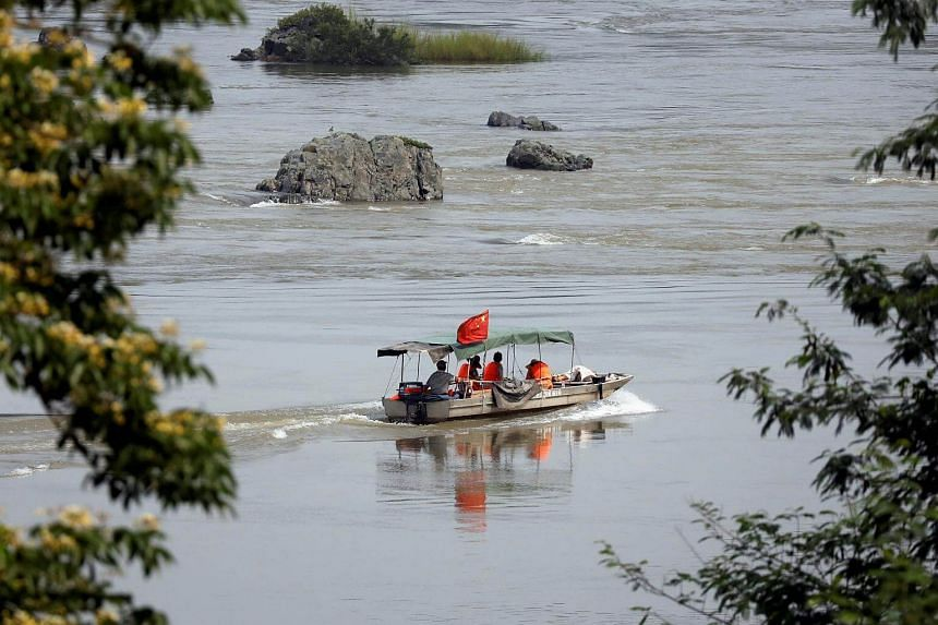 A Chinese boat with a team of geologists surveys the Mekong River.
