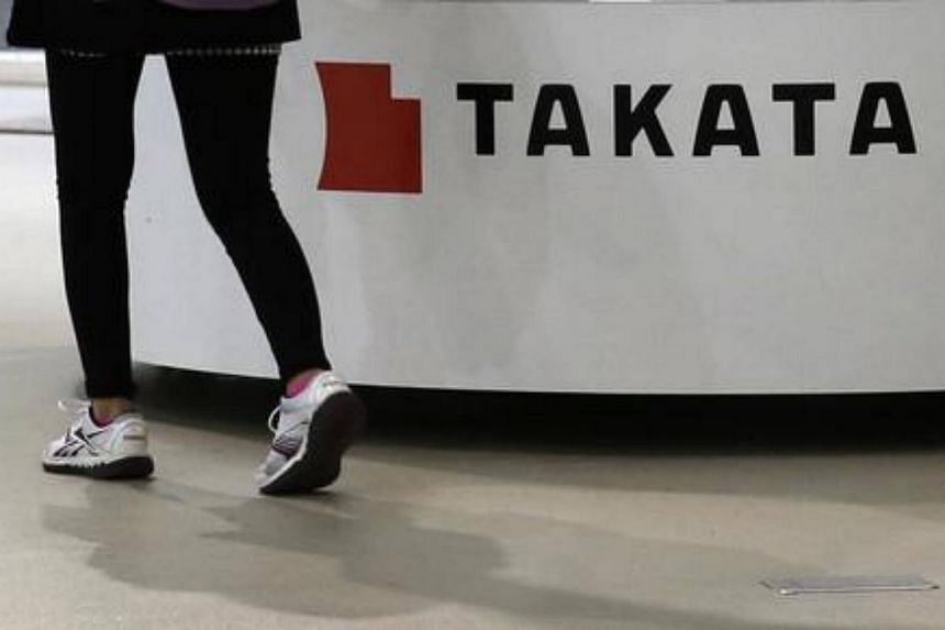 A visitor walks past displays of Takata Corp at a showroom for vehicles in Tokyo.