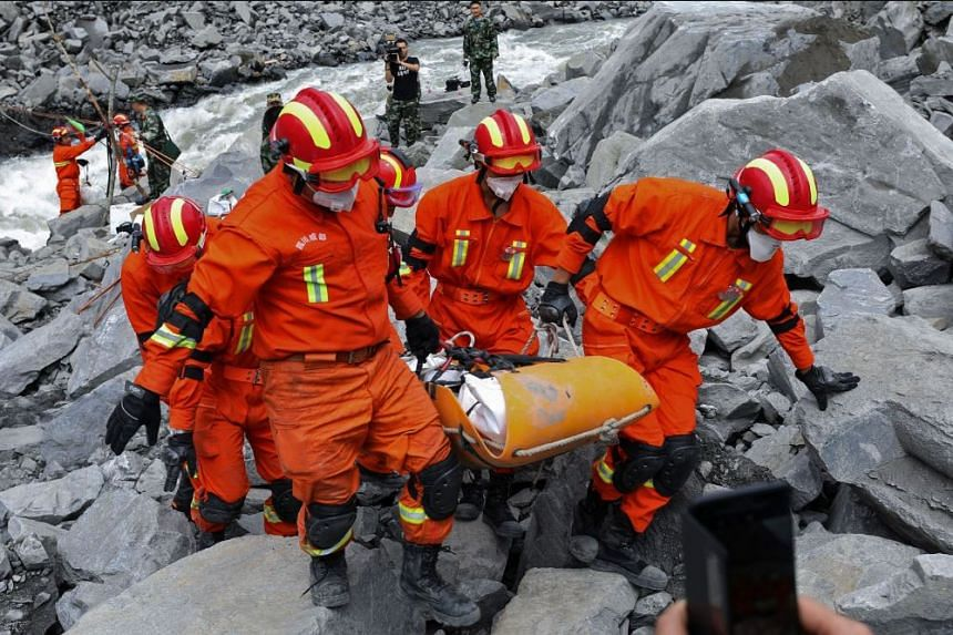 Rescue workers carry the body of a victim on a stretcher at the site of a landslide in Xinmo village, Diexi town of Maoxian county, Sichuan province on June 25, 2017.