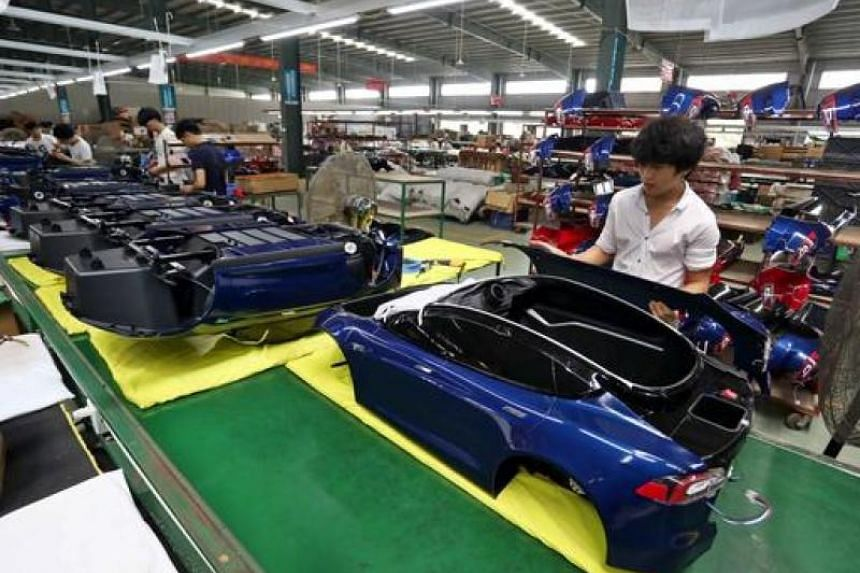 Workers assembling toy cars at a factory in Jinjiang, south-eastern China's Fujian province.