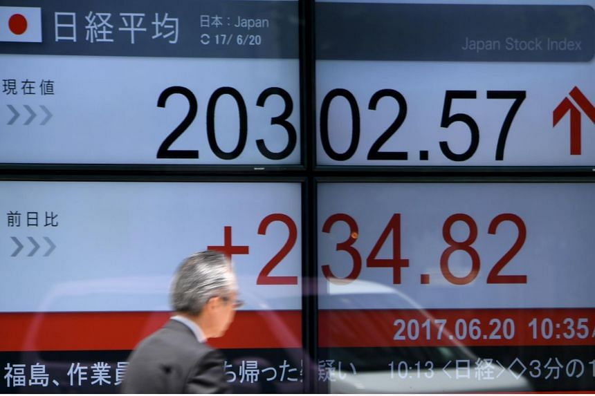 A man walks past an electronics stock indicator displaying the numbers on the Tokyo Stock Exchange.