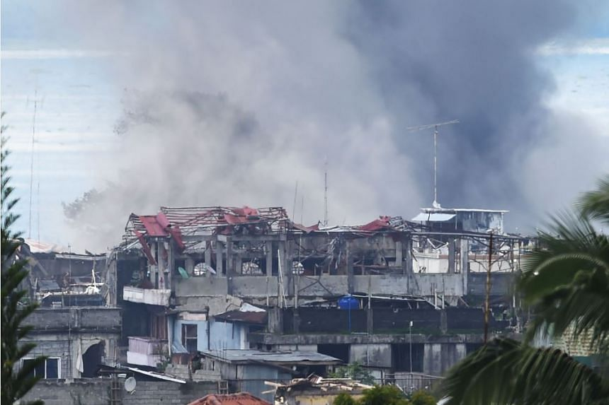 Black smoke billows from burning houses after an aerial bombing by the Philippine Air Force on militant Islamist positions in Marawi on the southern island of Mindanao on June 27, 2017.