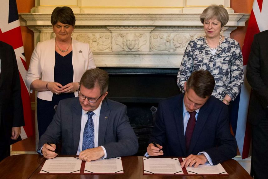 Britain's PM Theresa May (right) stands next to Democratic Unionist Party (DUP) leader Arlene Foster (left), as DUP MP Jeffrey Donaldson (second from left) sits and signs paperwork with Britain's Parliamentary Secretary to the Treasury, and Chief Whi