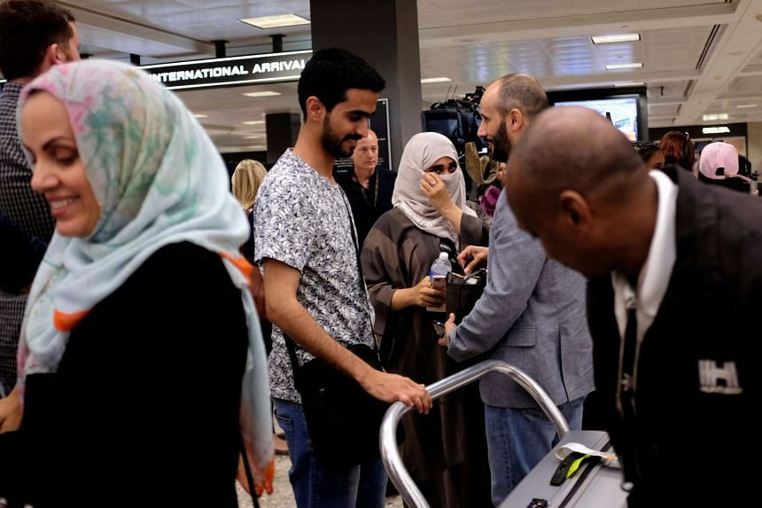 International passengers arrive at Washington Dulles International Airport after the US Supreme Court granted parts of the Trump administration's emergency request to put its travel ban into effect.