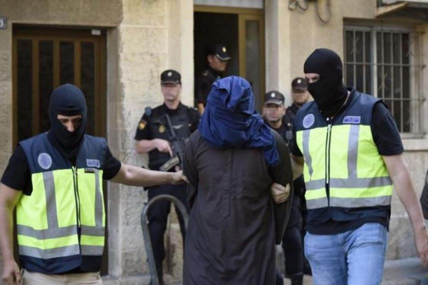 Policemen escort a suspect that was arrested as part of an international antijihadist police operation, in Palma Majorca, the Balearic Islands, Spain, on June 28, 2017.