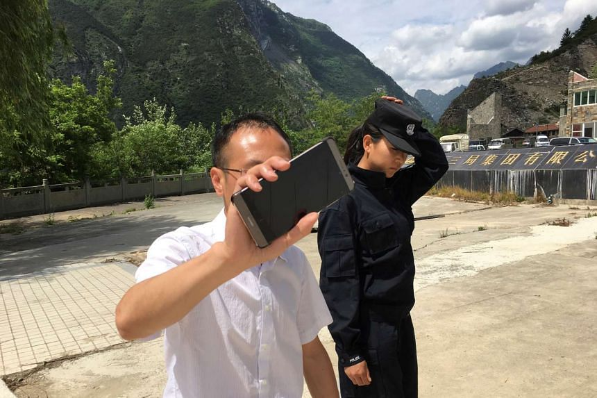 A local official and a police officer prevent journalists from accessing the site of the landslide, June 25, 2017.